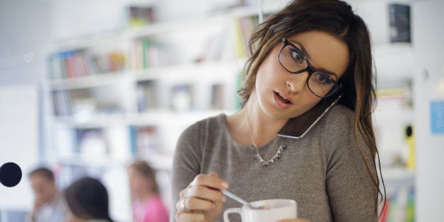 Buisnesswoman hearing bad news, while stirring coffee, people in background