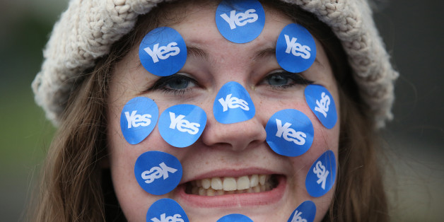 """A women wears stickers on her face on a """"short walk to freedom"""" march in Edinburgh, Scotland September 18, 2014. Polling in the referendum on Scottish independence began on Thursday morning, as Scotland votes whether or not to end the 307-year-old union with the rest of the United Kingdom. REUTERS/Paul Hackett (BRITAIN - Tags: POLITICS ELECTIONS TPX IMAGES OF THE DAY)"""