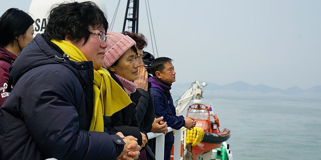 JINDO-GUN, SOUTH KOREA - MARCH 28: In this handout photo released by the South Korean Ministry of Oceans and Fisheries, Lee Geum-Hui (L), mother of Danwon High student Cho Eun-Hwa who went missing in the Sewol ferry looks at Sewol ferry as she stands on the deck of a boat on March 28, 2017 in Jindo-gun, South Korea. The Sewol sank off the Jindo Island in April 2014 leaving more than 300 people dead and nine of them still remain missing. Workers are in the process of an attempt to raise the ferry