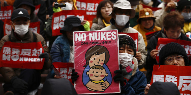 People hold placards denouncing nuclear energy during a rally in central Tokyo March 8, 2015. Anti-nuclear activists took to the streets on Sunday in Tokyo denouncing a planned restart of the country's nuclear reactors ahead of the fourth anniversary of the March 11, 2011 earthquake and tsunami disaster. REUTERS/Thomas Peter (JAPAN - Tags: CIVIL UNREST POLITICS ENERGY)