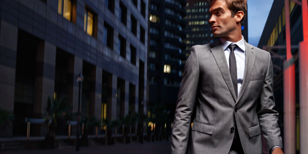 Shot of a handsome businessman in a suit walking through the city at night