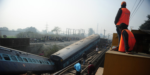 Indian officials and bystanders gather alongside derailed train carriages at Rura, some 30 kms west of Kanpur on December 28, 2016, following a train crash in the northern Indian state of Uttar Pradesh. At least two people died and 28 were injured after a train derailed in north India, close to the site of a previous rail accident that killed 146. / AFP / Sanjay KANOJIA        (Photo credit should read SANJAY KANOJIA/AFP/Getty Images)