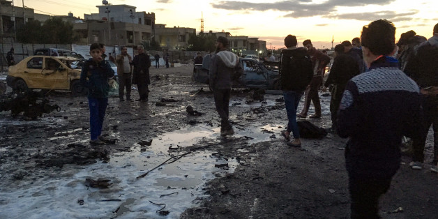 TOPSHOT - A picture taken with a mobile phone on February 16, 2017 shows locals looking through debris at the scene of a blast by a massive car bomb, which killed dozens in a used car market in southern Baghdad. The Amaq propaganda agency linked to the Islamic State group (IS), which has claimed nearly all such attacks recently, reported the blast and described it as targeting 'a gathering of Shiites'. / AFP / Ahmad MOUSA        (Photo credit should read AHMAD MOUSA/AFP/Getty Images)