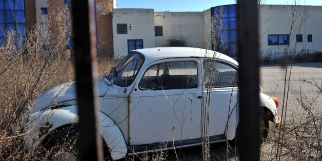 TO GO WITH AFP STORY BY VASSILIS KYRIAKOULIS Photo taken on January 15, 2015 shows a Volkswagen Beetle parked near a closed factory in Komotini, northern Greece. In Komotini, a city with a strong Muslim population, previously buzzing factories lie empty, the only movement that of looter gangs who strip the buildings bare of metals and machinery at night. 'Fifteen years ago, 17,000 people would come through the gates here to work,' says Pantelis Magalios, head of the Komotini trade union centre. 'Today there are barely 800 employees. And out of 100 businesses and factories, only ten are left,' he says. AFP PHOTO / SAKIS MITROLIDIS        (Photo credit should read SAKIS MITROLIDIS/AFP/Getty Images)