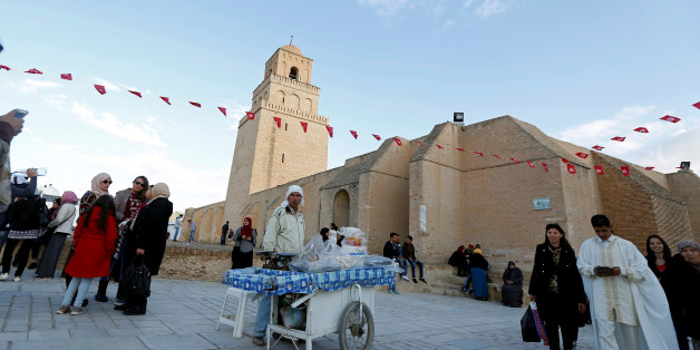People pass a street vendor selling traditional confectioneries in front of the Uqba ibn Nafi mosque, also known as the Great Mosque, during a celebration to mark the birthday anniversary of Prophet Mohammad, in Kairouan, Tunisia December 12, 2016. REUTERS/Zoubeir Souissi