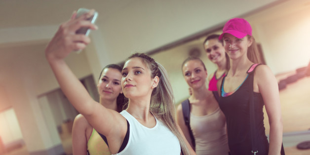 Group of young smiling athletic females how Taking Selfie in Gym after Exercise.