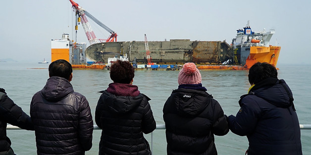 JINDO-GUN, SOUTH KOREA - MARCH 28: In this handout photo released by the South Korean Ministry of Oceans and Fisheries, Relatives of the missing victims look at a Sewol ferry on March 28, 2017 in Jindo-gun, South Korea. The Sewol sank off the Jindo Island in April 2014 leaving more than 300 people dead and nine of them still remain missing. Workers are in the process of an attempt to raise the ferry from the water in the hope that the disasters' final victims will be found. The Oceans Ministry says remains presumed to be of a victim of the Sewol ferry sinking have been found at the salvage site.  (Photo by South Korean Ministry of Oceans and Fisheries via Getty Images)