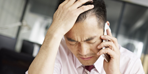 asian businessman talking on cellphone looking sad and frustrated.