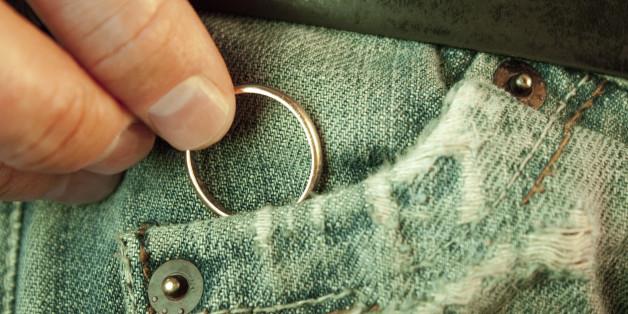 Closeup of a man?s hand put in or taking out a wedding ring in the worn jeans pocket. Concept of infidelity or asking in marriage.