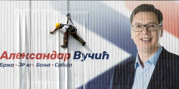 A worker installs on a wall an electoral poster of the Serbian Progressive Party (SNS) top candidate for the presidential election and Serbian Prime Minister Aleksandar Vucic in Belgrade on March 23, 2017.  Serbia's strongman Aleksandar Vucic hopes to win presidential elections in the first round on April2, 2017, to strengthen his political power despite criticism from divided opposition accusing him of authoritarianism.  / AFP PHOTO / OLIVER BUNIC        (Photo credit should read OLIVER BUNIC/AFP/Getty Images)