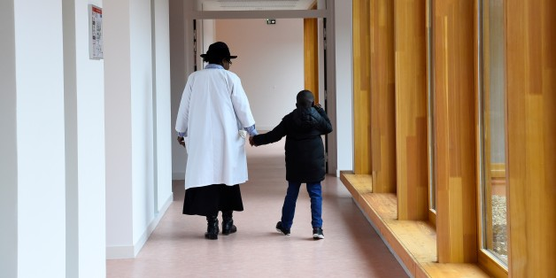 A nursing auxiliary and a child walk on March 21, 2017 in Neuilly-Plaisance, near Paris, in the new day hospital for autistic children.   / AFP PHOTO / BERTRAND GUAY        (Photo credit should read BERTRAND GUAY/AFP/Getty Images)