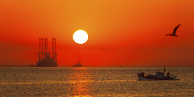 A traditional fishing boat and an offshore drilling rig during a colorful sunrise.
