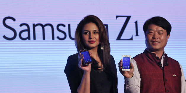 Hyun Chil Hong (R), president and chief executive of Samsung India Electronics, and Bollywood actress Huma Qureshi hold the Samsung?s new Z1 smartphones at its launch in New Delhi January 14, 2015. South Korea's Samsung Electronics Co Ltd has launched the first smartphone powered by its Tizen operating system, a major development in the tech giant's aim to build a software ecosystem to rival Google Inc's Android.   REUTERS/Adnan Abidi (INDIA - Tags: BUSINESS TELECOMS ENTERTAINMENT SCIENCE TECHNO