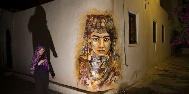 A woman walks past a mural by Spanish artist B-TOY in the village of Erriadh, on the Tunisian island of Djerba, on August 7, 2014, as part of the artistic project 'Djerbahood'. Nearly 100 artists from 30 different nationalities were invited by French-Tunisian organizer Mehdi Ben Cheikh to take part in an initiative to turn Djerba's Erriadh town into an 'open sky museum'. The village of Erriadh is one of the oldest in Tunisia where Jews, Muslims and Christians have lived together for centuries. A