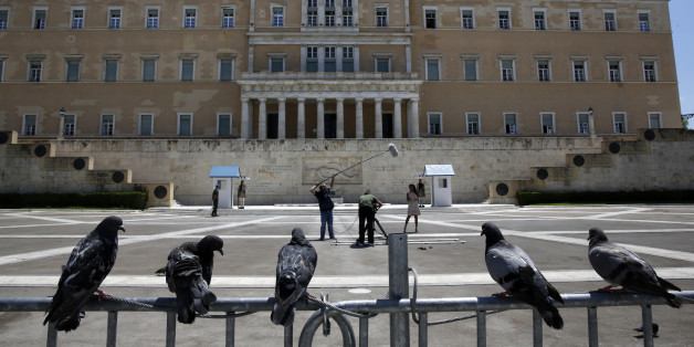 Pigeons perch on a police fence as a television crew films in front of the Greek parliament at an empty Syntagma (Constitution) square in central Athens during a visit by German Finance Minister Wolfgang Schaeuble July 18, 2013. Greek police have banned protests and traffic in downtown Athens on Thursday during a visit by Schaeuble, whom many accuse of forcing painful cuts on Greece in return for the multi-billion euro bailouts keeping it afloat.  REUTERS/Yannis Behrakis (GREECE - Tags: POLITICS