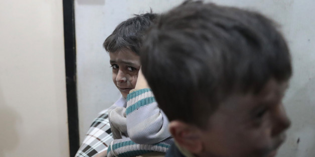 Syrian children wait to receive treatment at a makeshift clinic following reported air strikes by government forces in the rebel-held town of Douma, on the eastern outskirts of Damascus, on April 4, 2017. / AFP PHOTO / Abd Doumany        (Photo credit should read ABD DOUMANY/AFP/Getty Images)