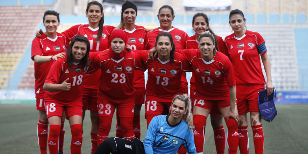 Palestinian female football players (in red) are seen during a qualifying match against Thailand for the Asian Women football Cup in the West Bank town of al-Ram on April 3, 2017.  The Palestinian women's football team saw a crushing defeat in their first match in Asian Cup qualifiers -- a 6-0 loss to Thailand -- but for captain Claudie Salameh, the score means little. 'Playing football for girls in Palestine is an enormous challenge,' she said after the match. Palestinian women football players