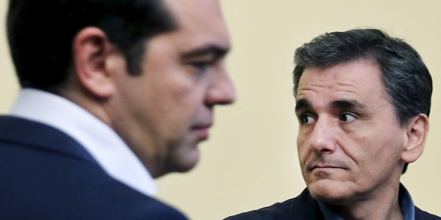 Newly-appointed Finance Minister Euclid Tsakalotos looks on during his swearing in ceremony as Greek Prime Minister Alexis Tsipras (L) stands next to him at the Presidential Palace in Athens, Greece July 6, 2015. Greece's top negotiator in aid talks with creditors, Euclid Tsakalotos, sworn in as finance minister on Monday after the resignation of Yanis Varoufakis. REUTERS/Alkis Konstantinidis      TPX IMAGES OF THE DAY