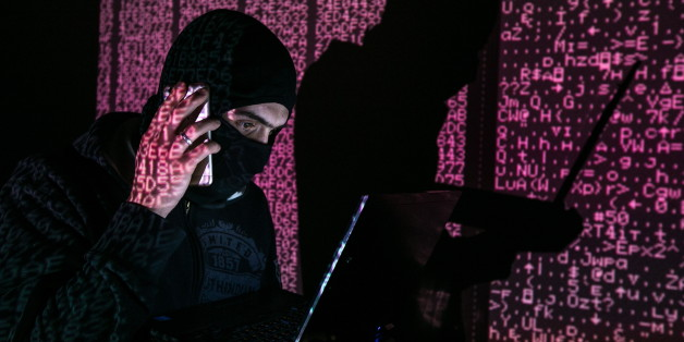 ST PETERSBURG, RUSSIA - FEBRUARY 6, 2017: A man in a balaclava mask sitting at a laptop computer, with computer code in the background. Sergei Konkov/TASS (Photo by Sergei Konkov\TASS via Getty Images)