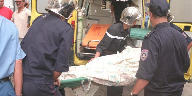 ALGIERS, ALGERIA:  Firemen carry the body of one of the victims of a bombing in central Algiers 31 August. The bomb exploded at the marketplace of the busy western district of Bab el Oued. The blast took place mid-morning killing at least 17 people and wounding 61. An estimated 80 000 people have died in violence since armed Moslem fundamentalists began a guerilla war in January 1992. (Photo credit should read AFP/Getty Images)