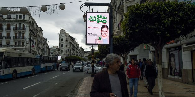 A picture taken on April 6, 2017 shows an illuminated billboard with the slogan 'make your voice heard' written in Arabic as pedestrians walk along a sidewalk in the Algerian capital Algiers.Campaigning starts on April 9, 2017 for Algeria's parliamentary polls in May, as authorities desperately try to persuade disillusioned voters that their opinion counts. Slogans reading 'make your voice heard' are found on on billboards and posters plastered in towns and villages across the North African coun