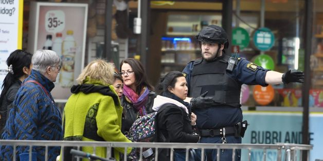 Police direct people after a truck crashed into the Ahlens department store at Drottninggatan in central Stockholm, April 7, 2017.