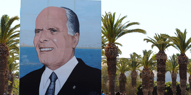 Tunisian wait next to a giant poster of former Tunisian president Habib Bourguiba as they attend an anniversary ceremony at the tomb on April 6, 2011 in Monastir. Tunisian leaders celebrate today the 11th anniversary of the death of the nation's father of independence Habib Bourguiba.   AFP PHOTO/ FETHI BELAID (Photo credit should read FETHI BELAID/AFP/Getty Images)