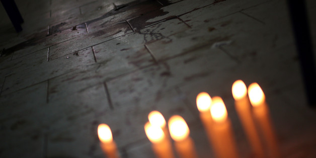 Candles are seen in front of the bloodstains of Rodrigo Quintana, who was killed last night by a rubber bullet fired by the police in the headquarters of the Liberal Party, after clashes in Asuncion, Paraguay, April 1, 2017. REUTERS/Marcos Brindicci