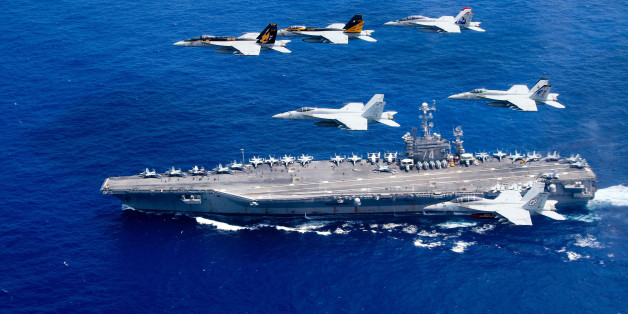 PHILIPPINE SEA - JUNE 18:  In this handout provided by the U.S. Navy, a combined formation of aircraft from Carrier Air Wing (CVW) 5 and Carrier Air Wing (CVW) 9 pass in formation above the Nimitz-class aircraft carrier USS John C. Stennis (CVN 74). The formation included F/A-18 Hornets from the Black Aces of Strike Fighter Squadron (VFA) 41, the Diamondbacks of Strike Fighter Squadron (VFA) 102, the Eagles of Strike Fighter Squadron (VFA) 115, the Royal Maces of Strike Fighter Squadron (VFA) 27