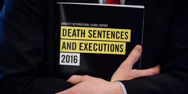 In this photo taken on April 10, 2017, a global report booklet by Amnesty International entitled 'Death Sentence and Execution' is held by James Lynch, deputy director of the Global Issues Programme at Amnesty International, after a media briefing at the Foreign Correspondents' Club (FCC) in Hong Kong. China executed more people in 2016 than all other nations combined, Amnesty International said on April 11, 2017, as death penalties in the world decreased overall.  / AFP PHOTO / ANTHONY WALLACE
