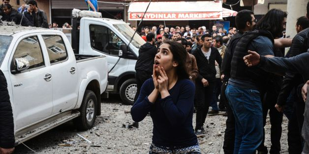 A woman reacts as she looks at the site of a strong blast near the riot police headquarters in the center of Diyarbakir, southeastern Turkey, on April 11, 2017. 