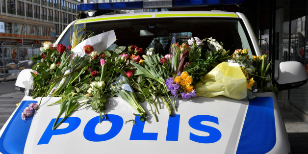 People leaving flowers on a police van outside Ahlens department store following Friday's terror attack in central Stockholm, Sweden, Sunday, April 9, 2017. Jonas Ekstromer/TT News Agency via REUTERS ATTENTION EDITORS - THIS IMAGE WAS PROVIDED BY A THIRD PARTY. FOR EDITORIAL USE ONLY. SWEDEN OUT. NO COMMERCIAL OR EDITORIAL SALES IN SWEDEN