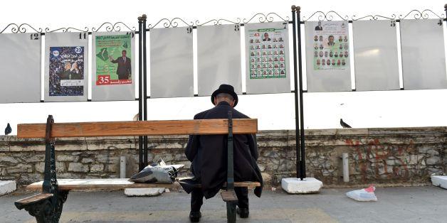 Un homme assis devant des panneaux de campagne électorale à Alger, le 9 avril 2017