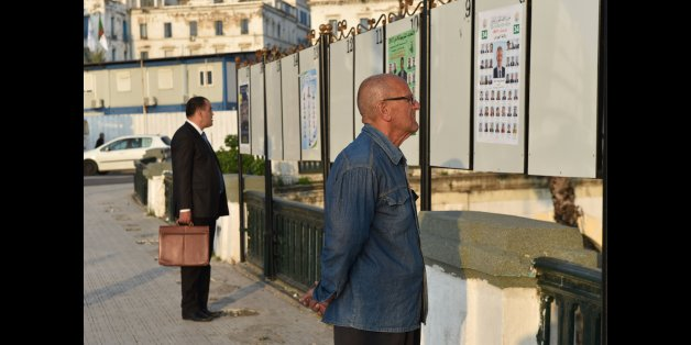Algerian men look at electorial campaign posters for the upcoming legislative elections in Algiers' Martyrs Square as the official start of campaigning got underway on April 9, 2017. / AFP PHOTO / RYAD KRAMDI / RYAD KRAMDI        (Photo credit should read RYAD KRAMDI/AFP/Getty Images)