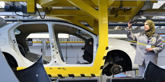 An employee of the French car maker Renault group takes a picture during the inauguration of a new production plant on November 10, 2014, in Oued Tlelat in the south of the Algerian city of Oran. The factory is to produce the Symbol, a saloon based on Renault's Clio compact sold mainly in markets where hatchbacks are not traditionally favoured. Production is destined for the Algerian market, Africa's second largest in terms of sales, with more than 400,000 vehicles imported every year. AFP PHOTO