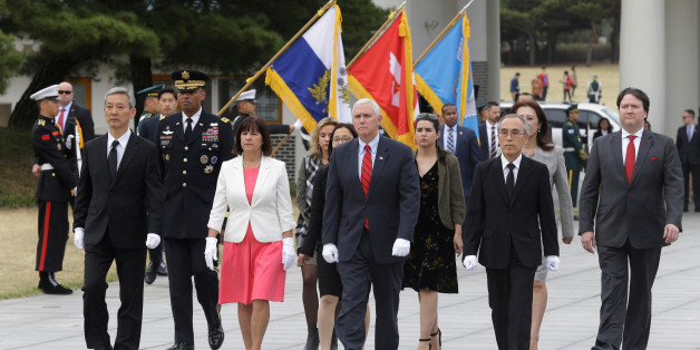 U.S. Vice President Mike Pence, center, and his wife Karen, center left, inspect hour guard upon their arrival at the National Cemetery in Seoul, South Korea, Sunday, April. 16, 2017. REUTERS/Ahn Young-joon/Pool