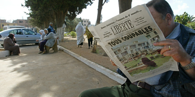 An Algerian reads the 26 May 2003 'Liberte' newspaper titled ' All guilty' 26 May 2003, at the entrance of El Alia cemetery in Algiers. The Algerian government scrambled Monday to dispel criticiem it has dragged its heels in helping victims of last week's deadly quake, as Islamic radicals took advantage of the widespread anger towards the authorities and stepped in to fill the void. AFP PHOTO/PHILIPPE DESMAZES        (Photo credit should read PHILIPPE DESMAZES/AFP/Getty Images)