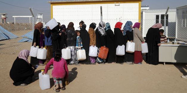 Internally displaced Iraqis, who fled the ongoing figthing between Islamic State (IS) group jihadists and government forces around Mosul, queue to fill containers with fuel for heating and cooking on November 28, 2016 at al-Khazer refugee camp.Some 70,000 civilians have fled the violence since Iraqi forces started the offensive to retake Mosul last month. / AFP / THOMAS COEX        (Photo credit should read THOMAS COEX/AFP/Getty Images)