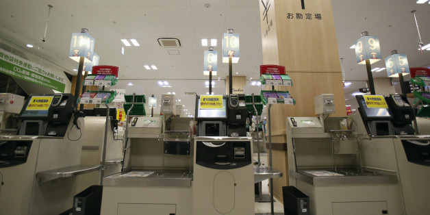 Self-service checkout machines, which are updated for a sales tax hike, are seen ahead of the store's opening hours at a branch of Aeon Co Ltd's supermarket in Chiba, east of Tokyo, April 1, 2014. Japan's sales tax will rise on Tuesday to 8 percent from 5 percent, the first increase in 17 years and the first step in a two-stage boost that is set to take the levy to 10 percent in 2015 as part an effort to curb the nation's massive public debt. REUTERS/Yuya Shino (JAPAN - Tags: BUSINESS POLITICS)