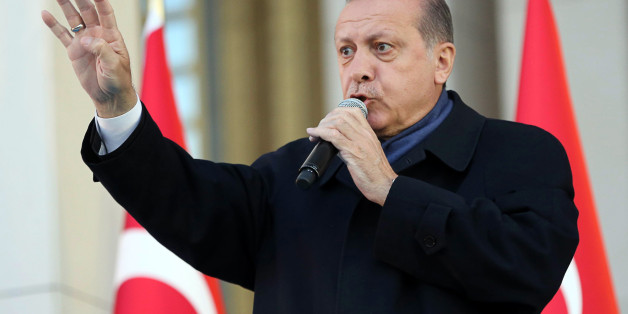 Turkish president Recep Tayyip Erdogan flashes a four finger sign called 'the rabia sign' as he delivers a speech to his supporters at the Presidential Palace in Ankara, April 17, 2017 following the results in a nationwide referendum that will determine Turkey's future destiny.Erdogan on April 17 said Turkey could hold a referendum on its long-stalled EU membership bid after Turks voted to approve expanding the president's powers in a plebiscite. Narrowly won by President Recep Tayyip Erdogan, t