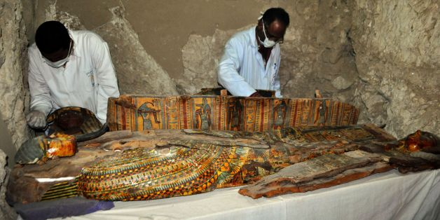 Members of an Egyptian archaeological team work on a wooden coffin discovered in a 3,500-year-old tomb in the Draa Abul Nagaa necropolis, near the southern Egyptian city of Luxor, on April 18, 2017.Egyptian archaeologists have discovered six mummies, colourful wooden coffins and more than 1,000 funerary statues in the 3,500-year-old tomb, the antiquities ministry said. / AFP PHOTO / STRINGER        (Photo credit should read STRINGER/AFP/Getty Images)