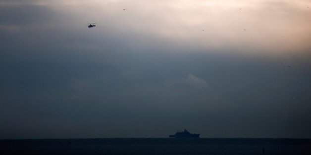 A helicopter flies next to a ship near the crash site of a Russian military Tu-154 plane, which crashed into the Black Sea on its way to Syria on Sunday, in the Black Sea resort city of Sochi, Russia, December 26, 2016.  REUTERS/Maxim Shemetov