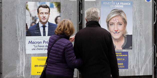 PARIS, FRANCE - APRIL 18:  A couple look at graffitied official campaign posters of Marine Le Pen, French National Front (FN) and political party leader and Emmanuel Macron, head of the political movement En Marche! (On move !), two of the eleven candidates who runs in the 2017 French presidential election on April 18, 2017 in Paris, France. French 2017 presidential election which will take place on April 23 and May 07, 2017.  (Photo by Chesnot/Getty Images)
