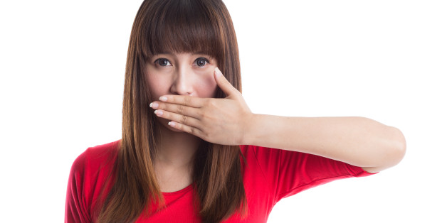 Beautiful young woman covering her mouth with her hand, isolated on white background