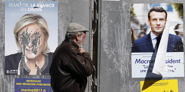 PARIS, FRANCE - APRIL 19:  A pedestrian walks past official campaign posters of Marine Le Pen, French National Front (FN) and political party leader and Emmanuel Macron, head of the political movement En Marche! (On move !), two of the eleven candidates who runs in the 2017 French presidential election on April 19, 2017 in Paris, France. Le Pen and Macron are candidates for the France's 2017 presidential elections and polls predict their presence in the second round of this election on May 07. (