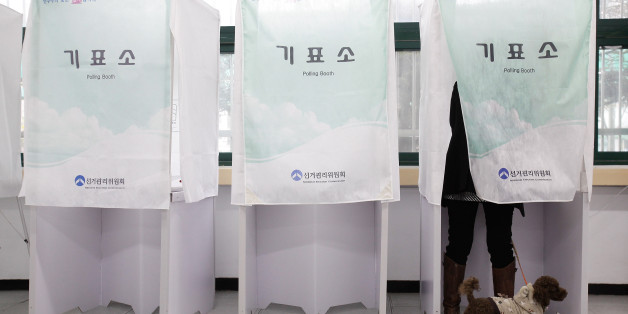 SEOUL, SOUTH KOREA - APRIL 11:  A South Korean woman casts her vote for new members of the National Assembly in a polling station at the Yuido Elementary School on April 11, 2012 in Seoul, South Korea. The poll is expected to be a tight contest between the two main South Korean parties, but neither New Frontier Party or its main rival, the Democratic United Party are likely to win a majority in the 300 seat assembly.  (Photo by Chung Sung-Jun/Getty Images)