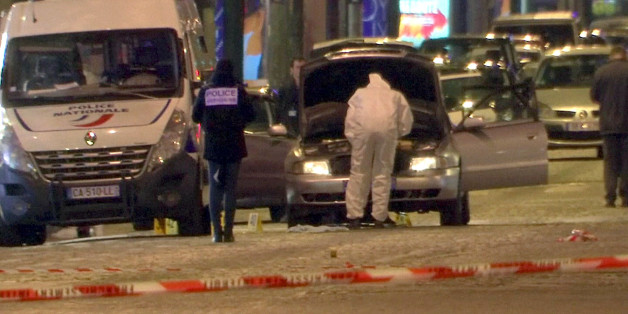 A still image from video footage shows Police investigators inspect the car used by the attacker on the Champs Elysees Avenue after a policeman was killed and two others were wounded in a shooting incident in Paris, France, April 20, 2017.    REUTERS/Reuters Tv