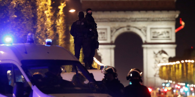 Masked police stand on top of their vehicle on the Champs Elysees Avenue after a policeman was killed and two others were wounded in a shooting incident in Paris, France, April 20, 2017. REUTERS/Christian Hartmann   TPX IMAGES OF THE DAY