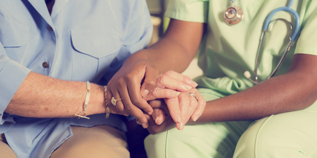 Caring home healthcare nurse conducts medical consultation with senior adult woman at her home or nursing home.  The elderly female patient is being comforted by the African descent nurse as she is holding her hands as they talk together. Focus on hands.  Vintage look.
