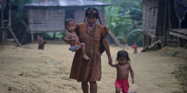 An Embera indigenous woman walks with her children in Puesto Indio, a rural village in Alto Baudo, department of Choco, western Colombia, on January 25, 2017.